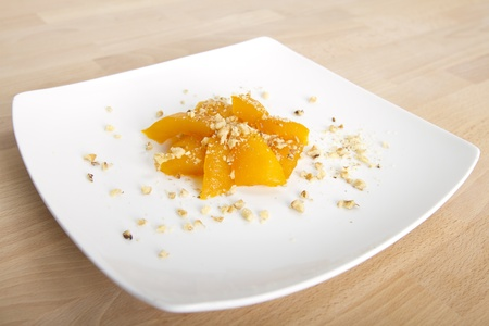 Home made Turkish traditional pumpkin dessert complimented with walnuts on large white plate on beech wood table. photo
