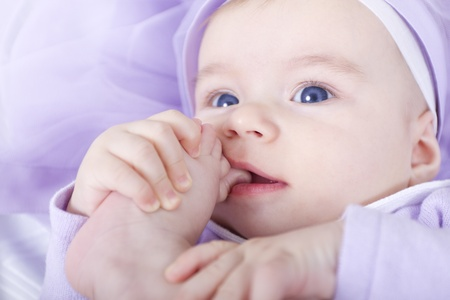 Blue eyed six months old lady holding her toe in her mouth. Wearing Purple Dress and purple background.