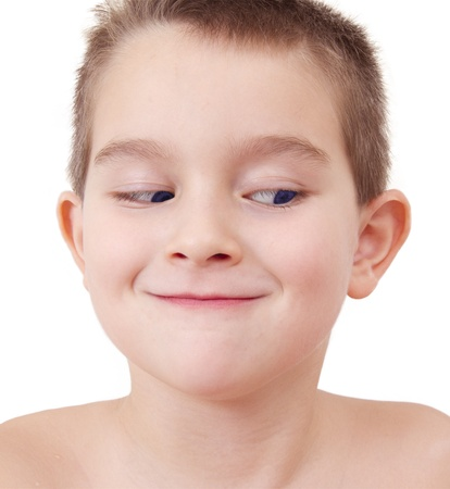 Mischievously smiling and looking sideway down kid is up to something. Stock Photo - 12190906