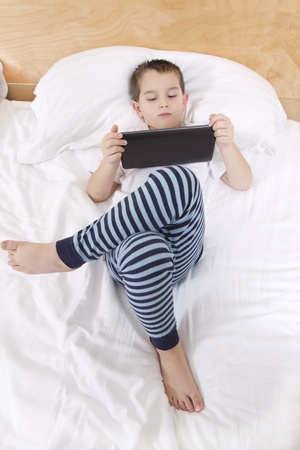 rest in peace: Elementry school boy reading his tablet before he goes to bed