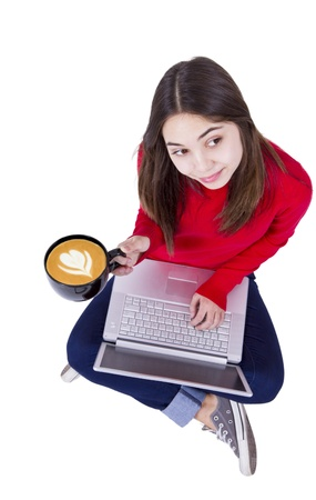 Teenager gorl is holding her  Froth Art  latte coffee and laptop on the floor. Stock Photo - 12190931
