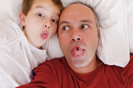 twist: Father and son having fun in the bed by rolling their tongues.