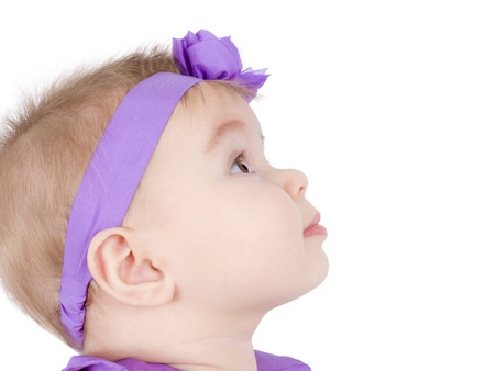 abstruse: Pretty little girl is in her headband observing something, perhaps her parents. Stock Photo