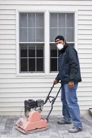 compacting: Man with protection mask compacting pavers. Stock Photo