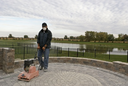 pavers: Man with protection mask compacting pavers. Stock Photo