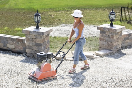 compacting: Woman with the white hat compacting patio base under the sun. Stock Photo