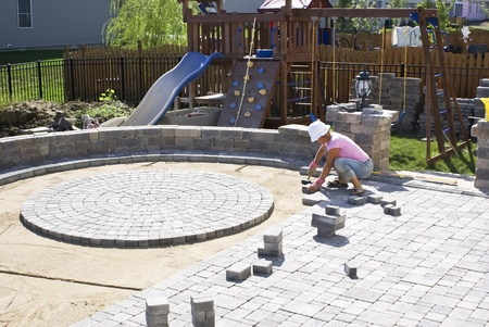 construction project: Woman with the white hat paving patio at the backyard of their house. Editorial