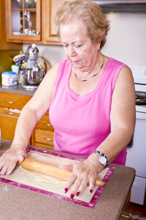 Older lady prepearing Turkish Pide pockets dough in the kitchen.