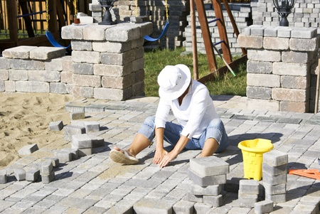 Woman with the white hat paving patio under the sun.