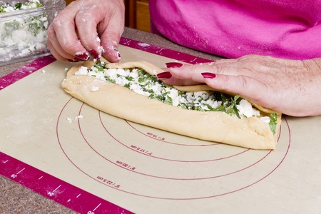 Older lady hands are wrapping Turkish feta cheese Pide pockets.