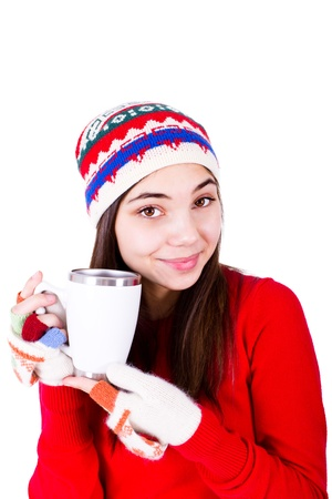 heats: Young girl in winter clothes holding a coffe cup with copy space on it  Wearing Winter hat and fingerless glowes  Isolated on white background