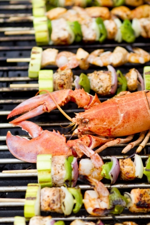 prawn skewers: Lobster and fish skewers are on the barbecue. Stock Photo