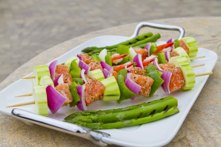Salmon cubes and Shrimp complimented with vegetables on skewers. Red onions, zucchini, green peppers and asparagus. On white modern plate placed on concerete countertop. photo