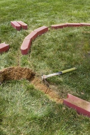 Installing brick edging with one side rounded bricks by removing the grass. photo
