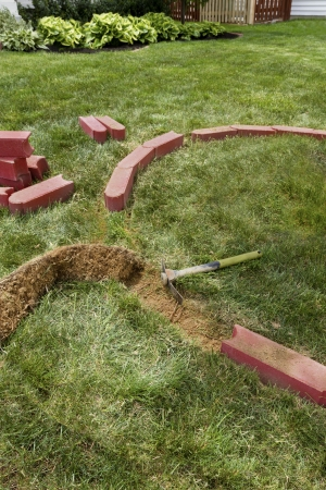 Laying brick edgers around the house for easy trimming and cutting the grass. photo