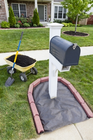 Laying mulch around the mailbox and placing edger bricks. photo