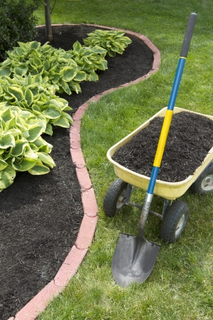 Mulch bed around the house and wheelbarrel along with a showel. photo