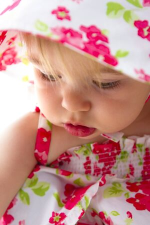 Baby looking deeply with her lovely cheeks and red lips with red flower dress. Stock Photo - 14260881