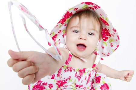 Little baby girl with pretty red flower dress and hat handing over her sun glasses to you. Stock Photo - 14260884