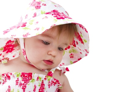 Baby looking thoughtfully simple in her red and green on white flower dress and matching hat. Stock Photo - 14260877