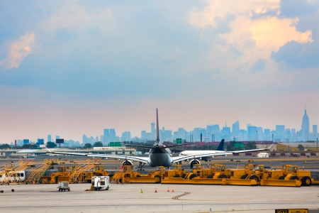 servicing: Airports runway and ground services waiting to service. With an airplane in-front of city.