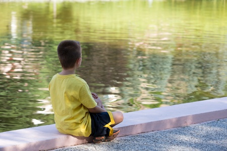 He is alone or lonely, seven years old kid looking at calm water while in deep thoughts.