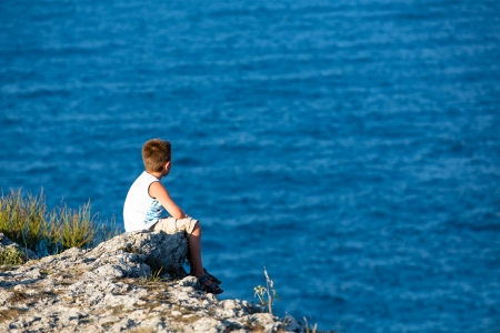 lonely boy: Young kid watching the Black Sea, He is high on the rocks.