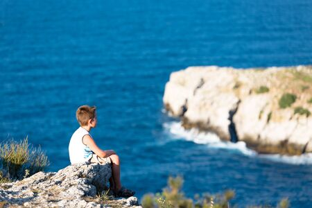 Young kid peacefully watching the waves of Black Sea. He is high sitting on the rocks.