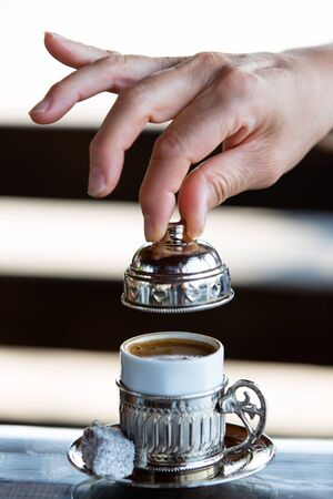turkish delight: Turkish Coffee served in silver housing with a Turkish delight and ready to take a sip. Clean hands elegantly removing the cap.