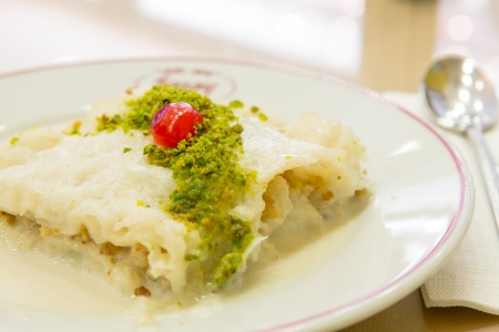 Traditional Turkish Ramadan dessert gullac made with Phyllo Dough and sweetened milk, served with pistachio crumble and complimented with a piece of cherry. Stock Photo