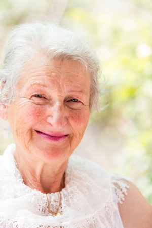 wise woman: Grandmother looking at you confidently with her white hair and complimenting nice clothing. Stock Photo