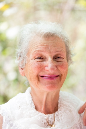 Grandmother looking at you happily  with her white hair and complimenting nice clothing. Banco de Imagens