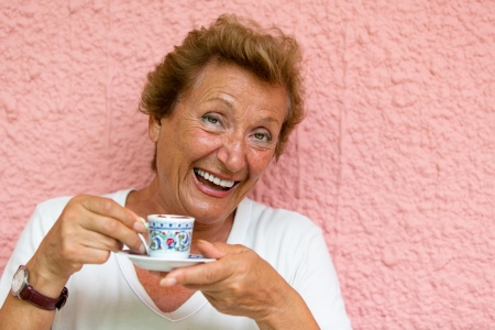 turkish woman: Older lady drinking her Turkish Coffee and giving caffeinated look