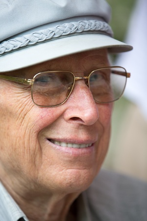 Senior man is smiling at camera with his classic gray hat and golden color glasses Stock Photo - 15783923