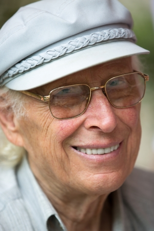 Senior man smiling at camera with his hat and glasses  photo