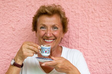 turkish woman: Older Lady drinking her Turkish coffee infront of pink  textured wall Stock Photo