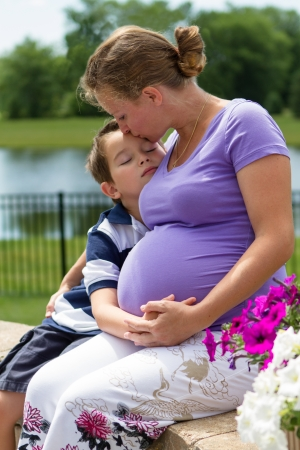 kissing pregnant belly: Pregnant woman holding her belly with her son while kissing him. Stock Photo