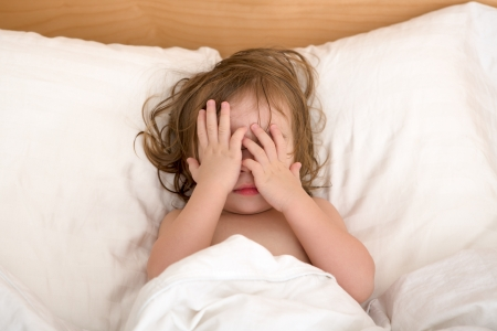 Toddler Girl closing her eyes in the bed, perhaps she is seeing bad dreams. Stock Photo