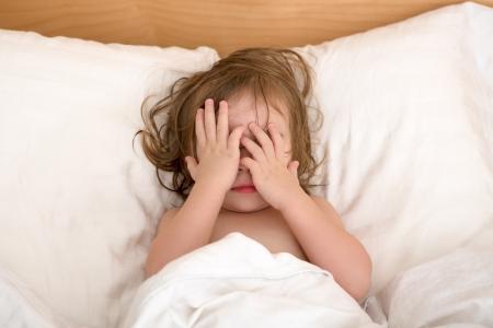 Toddler Girl fermant les yeux sur le lit, peut-être qu'elle voit de mauvais rêves. Banque d'images