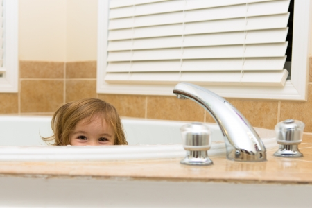 Toddler girl giving happy hiding look from the bathtub, perhaps she does not want to take a bath Stock Photo - 18162531