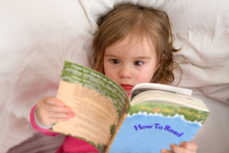 Cute Ttoddler reading her stories before she goes to sleep. Big eyes carefully looking in to letters while her mind moves fast. Perhaps she is speed reader. Reading habits starts with early age. photo