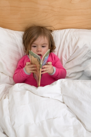 Reading habits starts with early age, cute toddler is just browsing the pages in her pink pajamas before she goes to sleep. photo