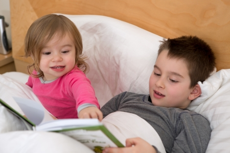 Little sister pointing a page to his older brother in the book before they go to sleep.