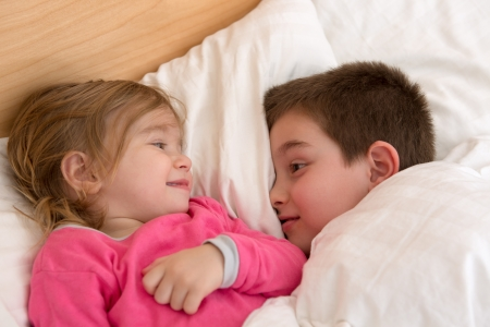 eachother: Siblings looking at eachother in the bed, happy cozy moments. Stock Photo