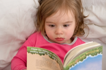 Cute Ttoddler reading her stories before she goes to sleep  Reading habits starts with early age  photo