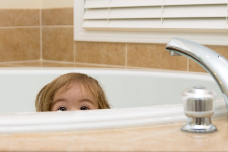 Toddler girl giving curious expression while hiding in the bathtub Stock Photo - 18162530