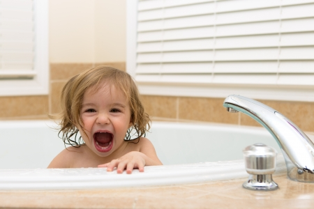 Toddler girl laughing cheerfully her moth open from bath tub  Teething Archivio Fotografico