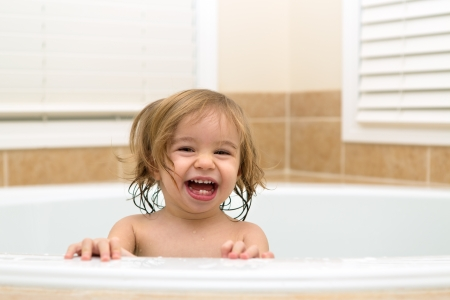 hiding face: Toddler girl laughing happyly from bath tub,