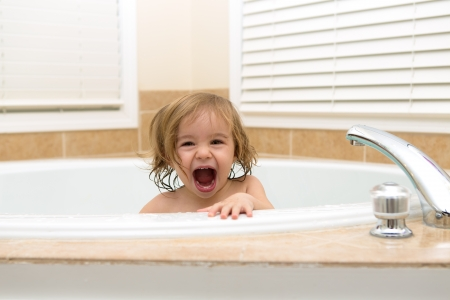 Toddler girl laughing cheerfully from bath tub