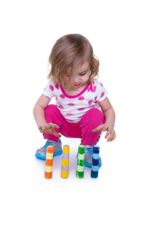 perceptual: Toddler learning motor skills by paying attention to colorful crayons. Isolated on white with copy space.